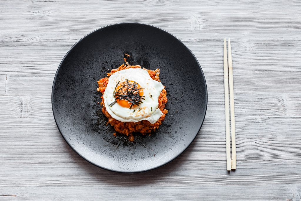 Kimchi bokkeum bap on black plate and chopsticks