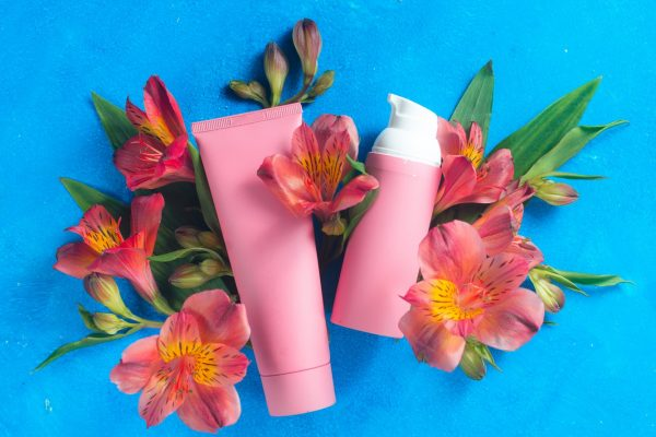 Skin care cosmetics in pink palette in on a blue background with spring flowers. Natural cosmetics